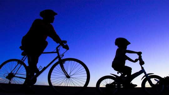 אבא ובן רוכבים על אופניים בשקיעה