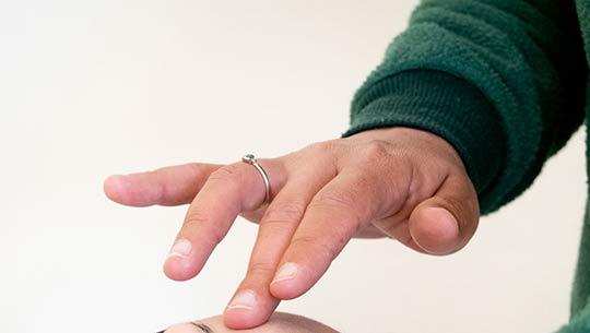 אצבע אמצעית נוגעת במצח של מטופלת