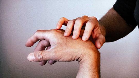שיטת איזון חיים - מגע לאיתור סימני הדרך של הגוף - יד המטפלת פורטת על היד של המטופל לאיתור נקודות כאב