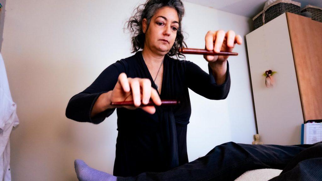 ליאת מחזיקה מקלות מעל מטופל בשיטת איזון חיים