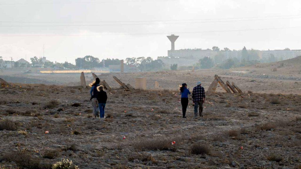 ארבעה אנשים הולכים לכיוון מצפה רמון מהמדבר, כשברקע מגדל המים וקו הבניינים של השכונות