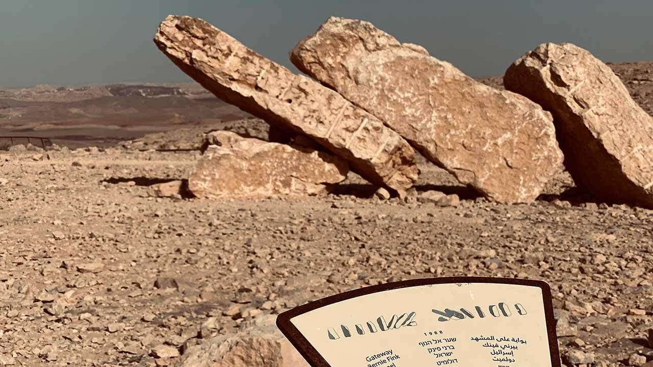 שלט מול פסל עשוי מאבנים גדולות
