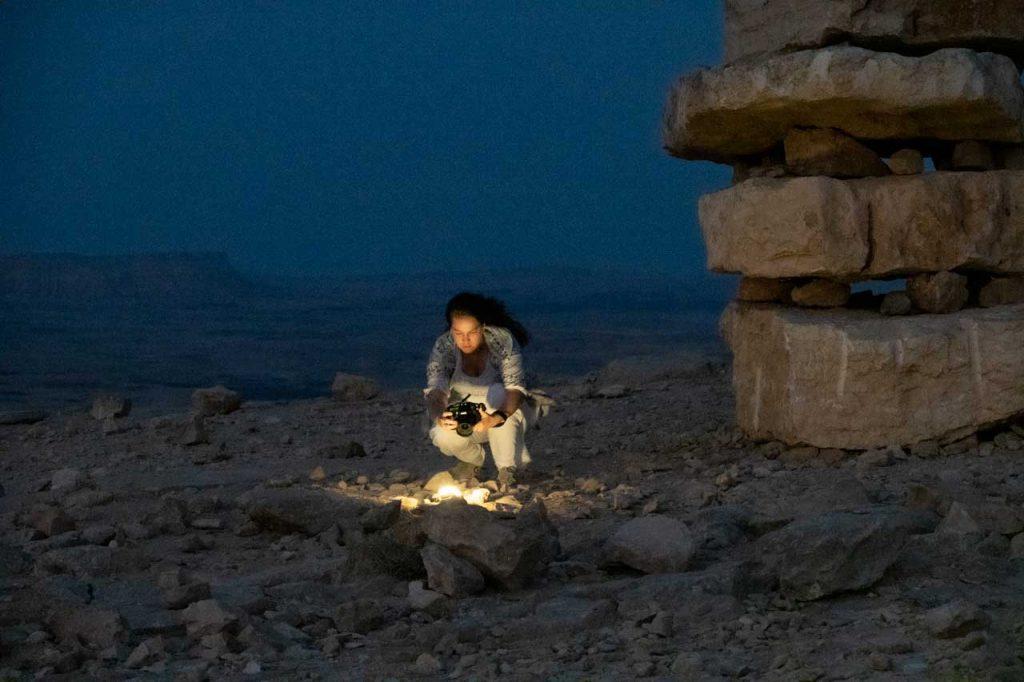 אישה מצלמת במדבר מקור אור בשעת ערב