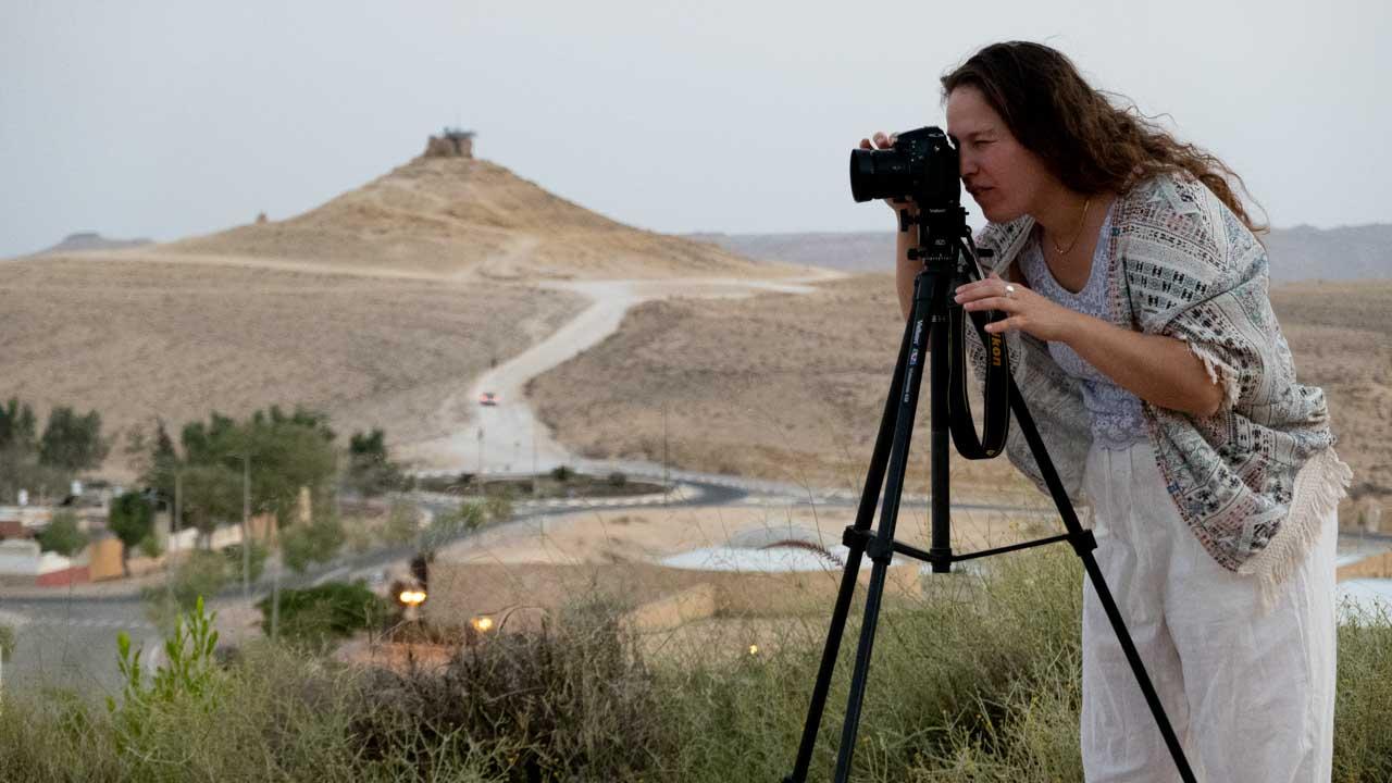 אישה מצלמת על רקע נוף מדברי של הר גמל במצפה רמון