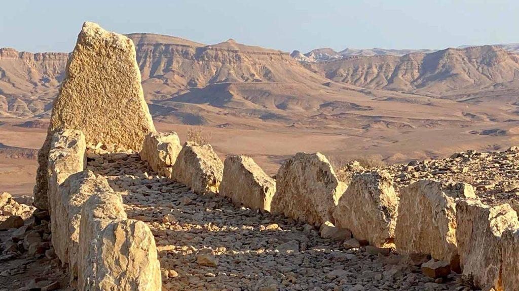 שתי שורות אבנים שמתכנסות לשביל שמוביל לסלע בקצה