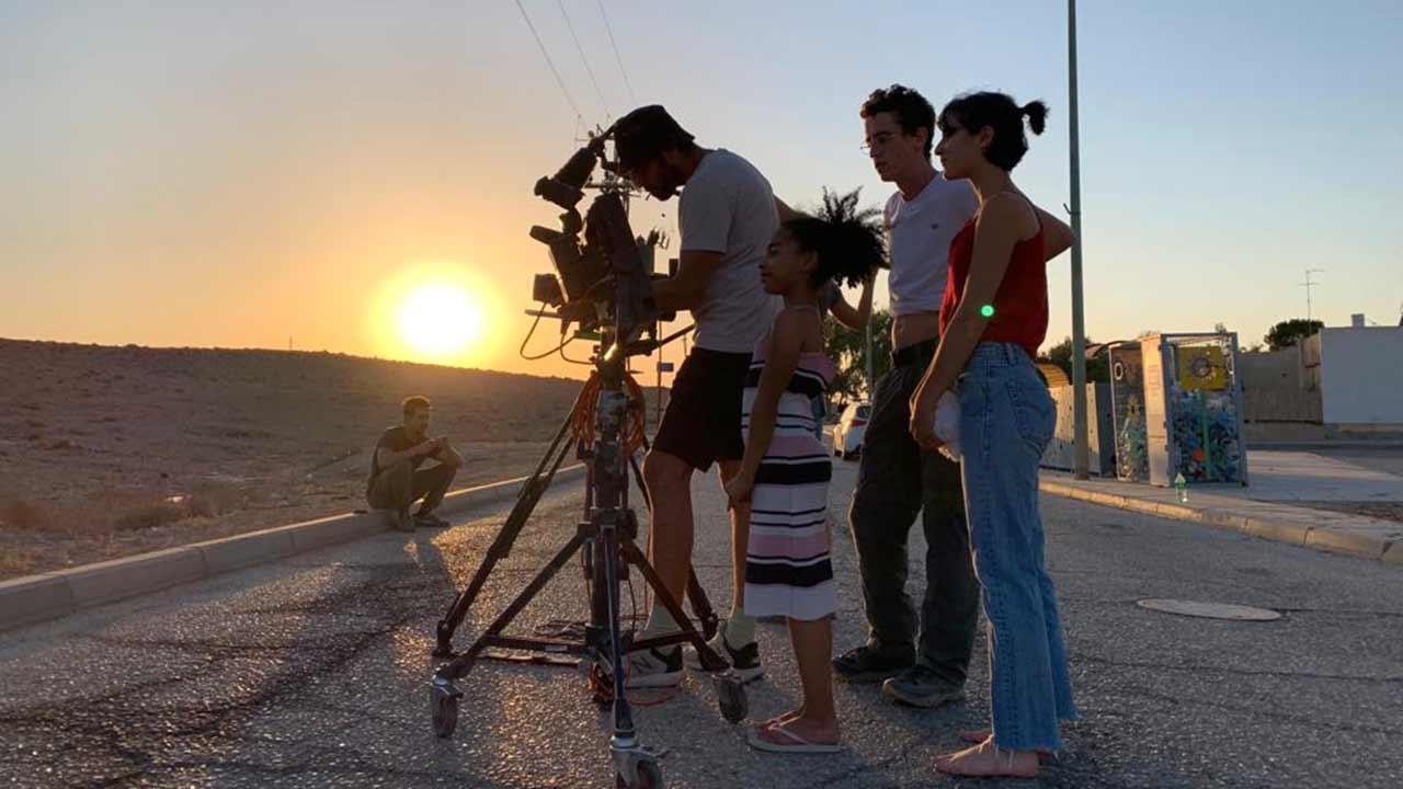 שלושה אנשים במדבר עם מצלמת קולנוע ושקיעה ברקע