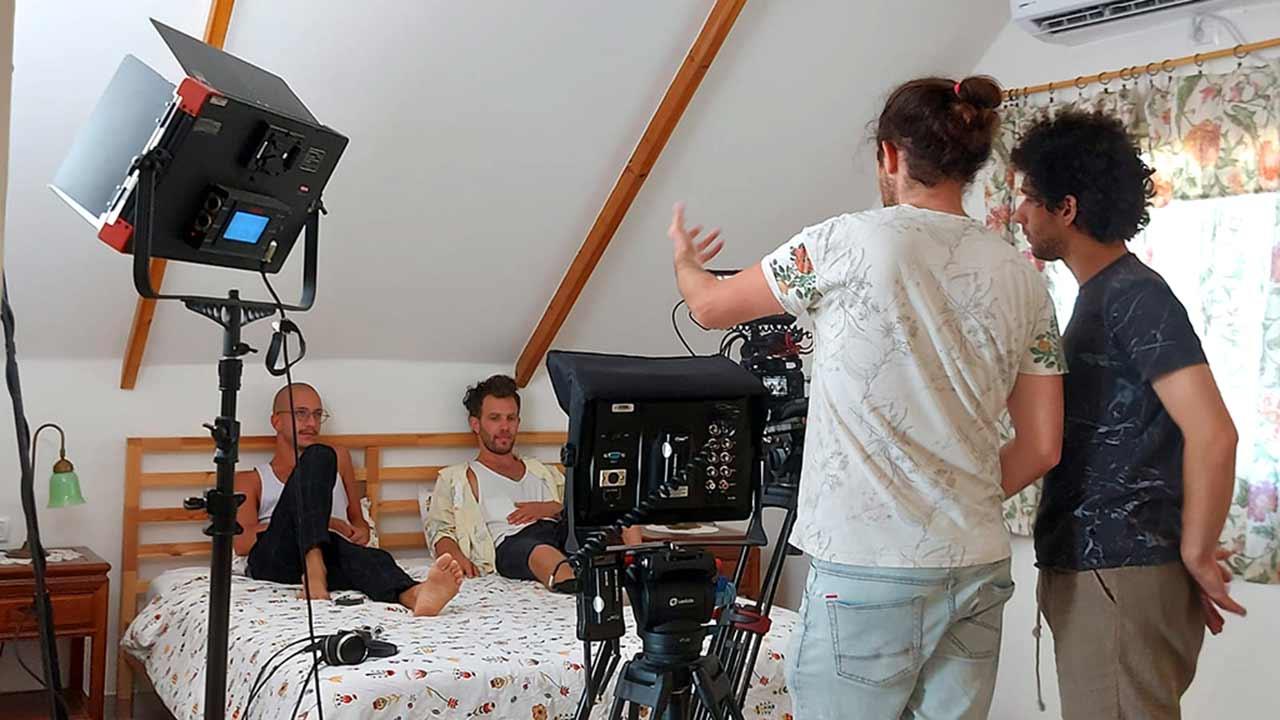 שני גברים על מיטה ואיש שלישי מצלם אותם במצלמת קולנוע. כל זה קורה בעליית גג.