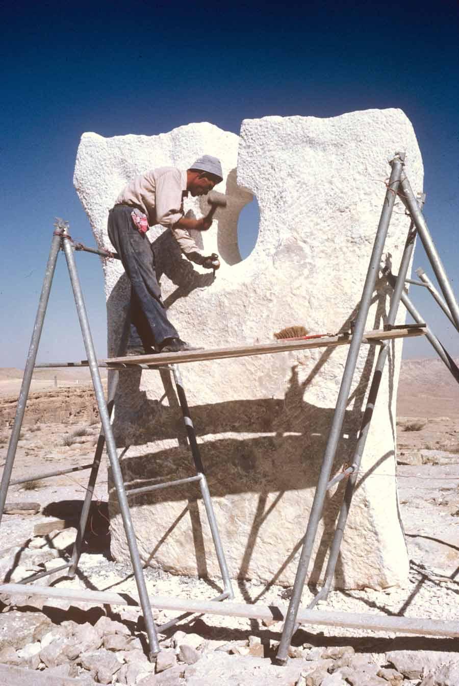 אדם מפסל פסל בעמדו על קלונסאות במדבר